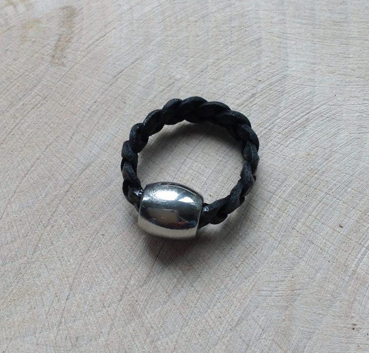 leren gevlochten ringetje met een zilverkleurige bedel